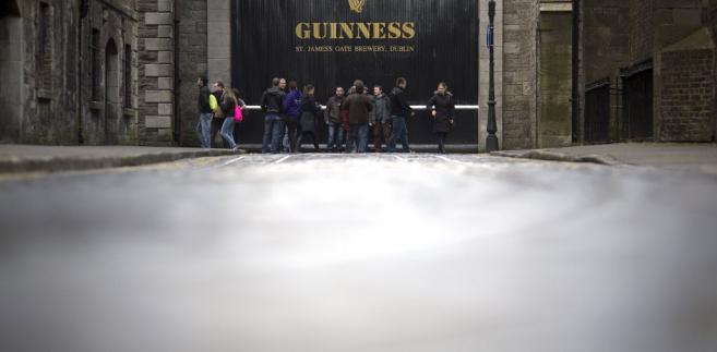 Dublin, Irlandia. Na zdjęciu: przechodnie i turyści przed bramą browaru Guinness St. James's Gate Brewery, należącego do Diageo Plc.