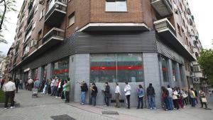 Bezrobotni stoją w kolejce do urzędu pracy w Madrycie