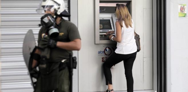 Kobieta wypłacająca pieniądze z bankomatu. Grecja, 2.07.2015